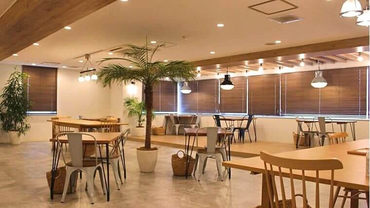 イングリッシュカンパニー横浜スタジオ内の写真。トレーニングを行うオープンスペースの画像。カフェのような雰囲気の部屋に椅子とテーブルが並んでいる。