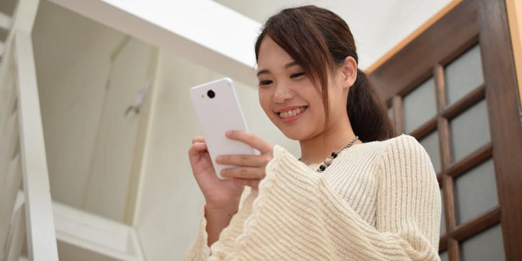 スマホでチャットを楽しむ日本人の女の子の画像